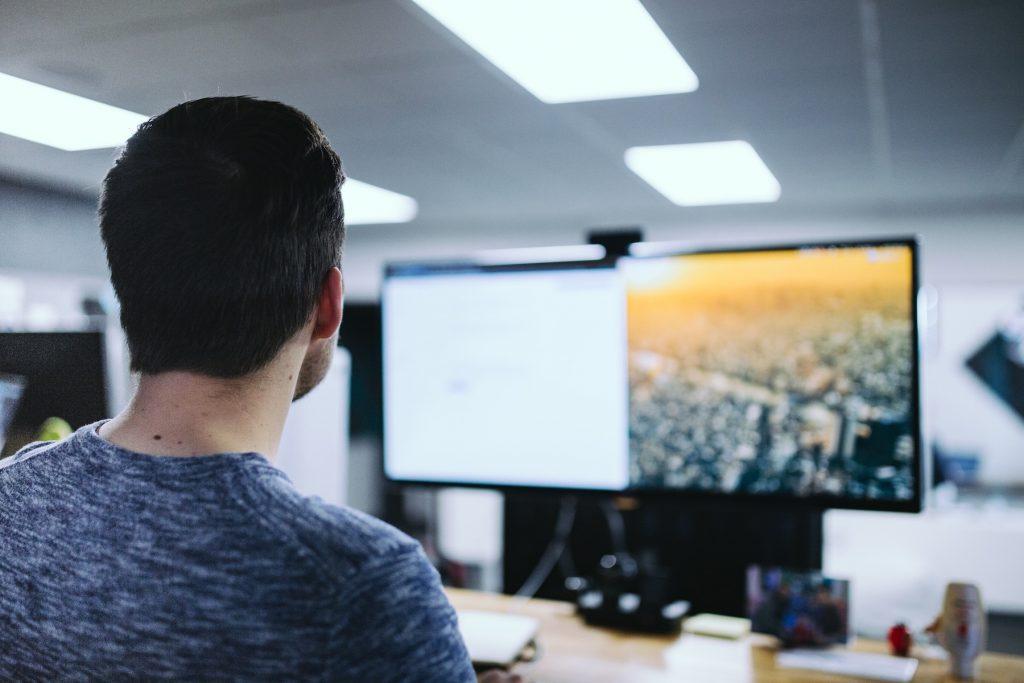 Man looking at computer monitors