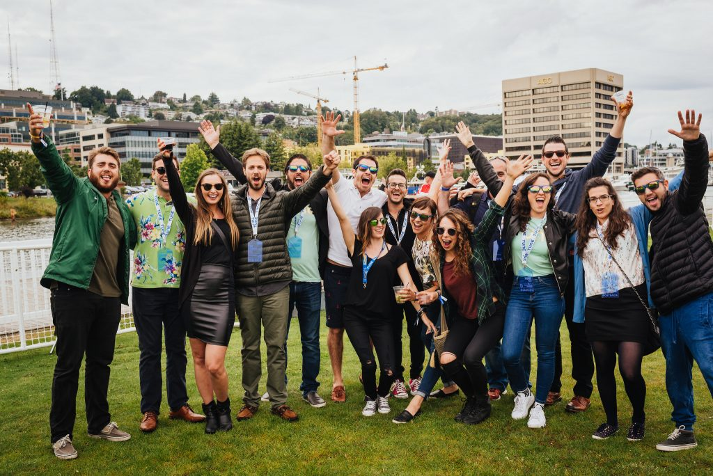 A group of attendees cheer for a photo during a lawn party at Postback 2016