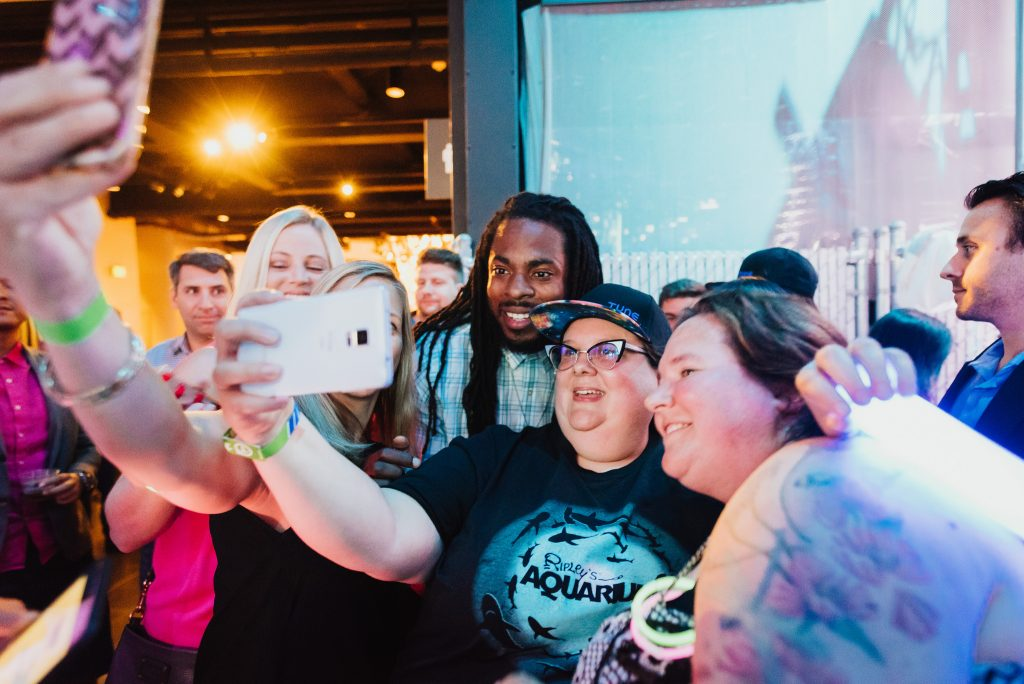 Richard Sherman poses with fans at a music event during Postback 2016