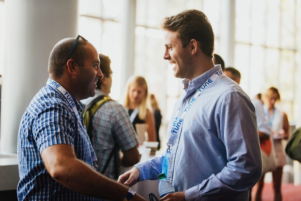 Two men shake hands as they network at Postback 2016