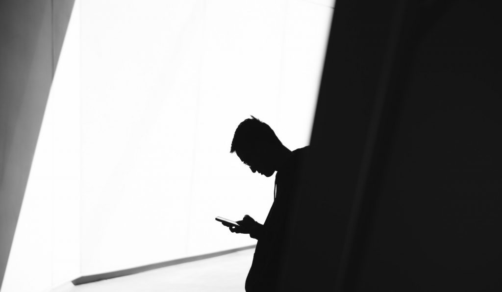 Photo of man holding mobile phone in shadow