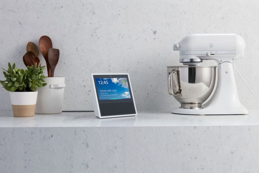 An Amazon Echo Show sits on a kitchen counter next to a mixer.
