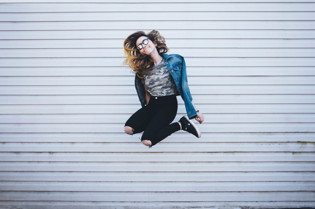 A girl jumps in front of a white wall.