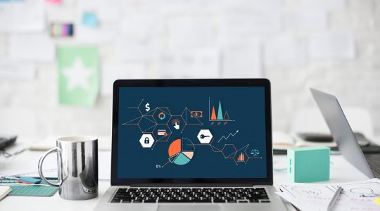 A computer with graphs and charts represents performance marketing.