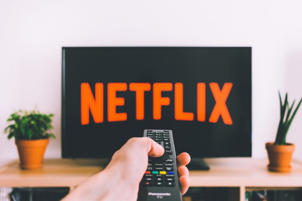 Hand holding a TV remote in front of a Netflix screen