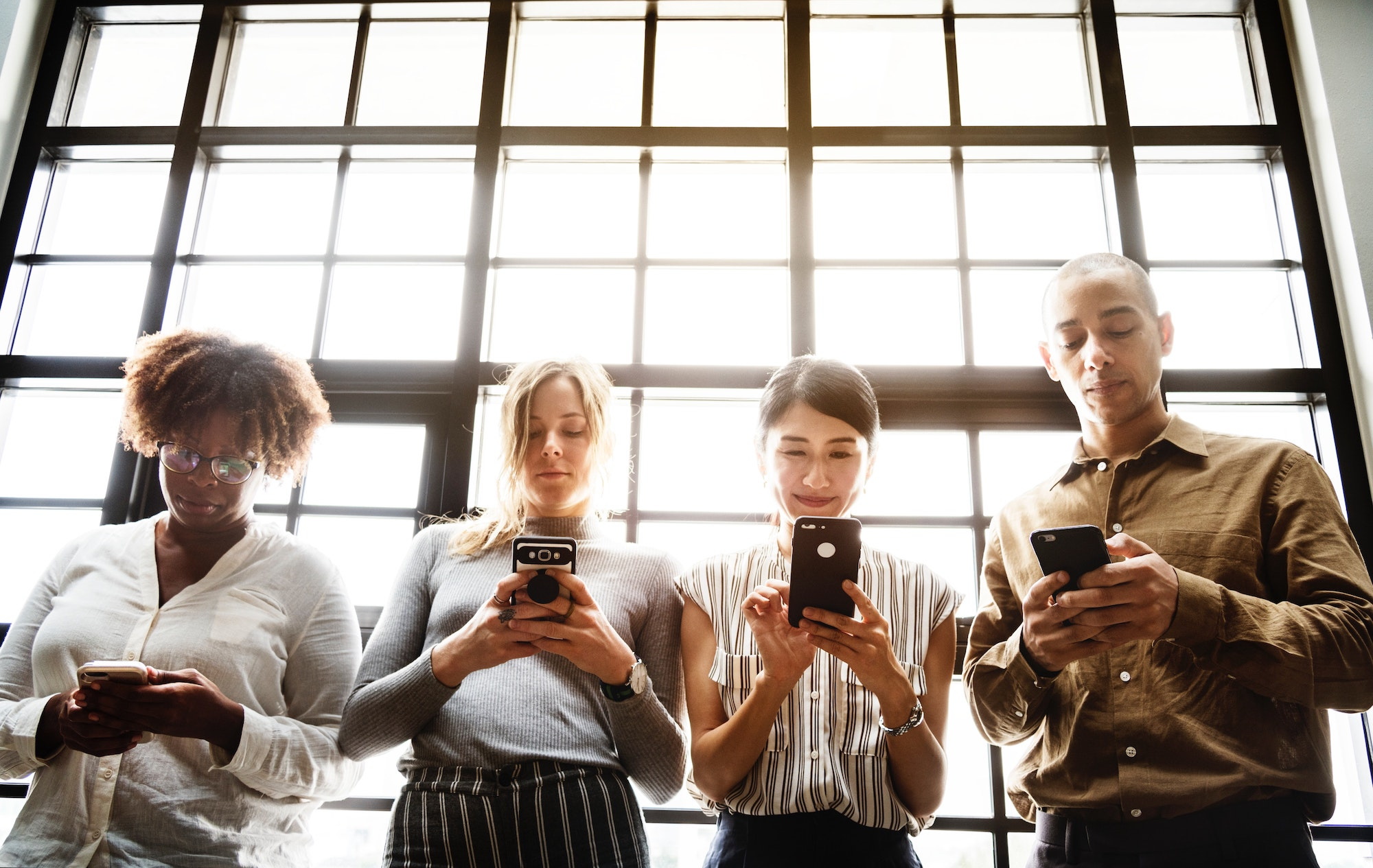 Four people browse smartphones backlit by window panes